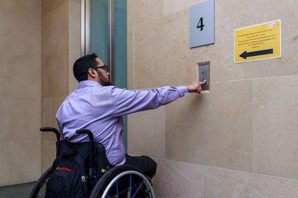 Man in a wheelchair calling an elevator