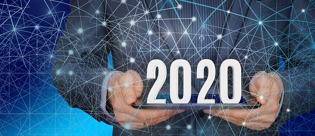 A man holds a tablet and 2020 in 3D appears. There are patterns across the photo