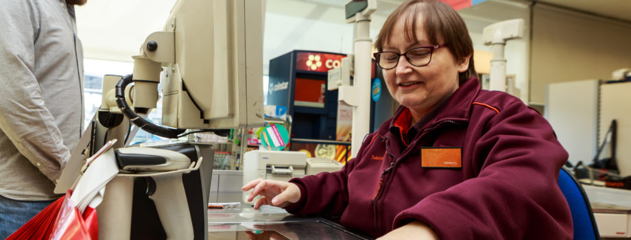 Image of a Sainsbury's cashier serving a customer
