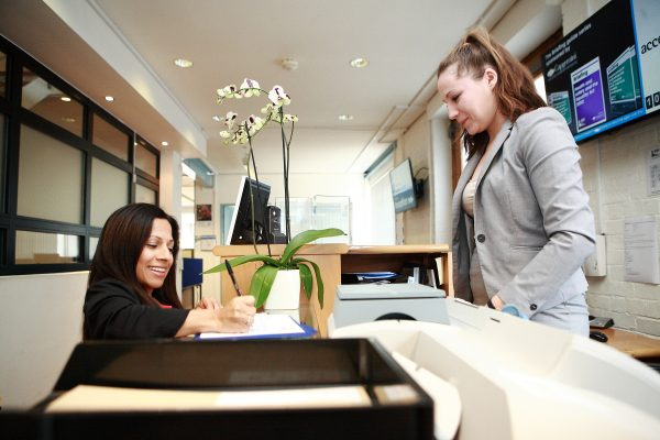 Image of two people at reception desk