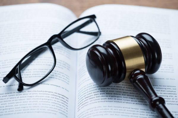 Gavel and a pair of glasses on an open book