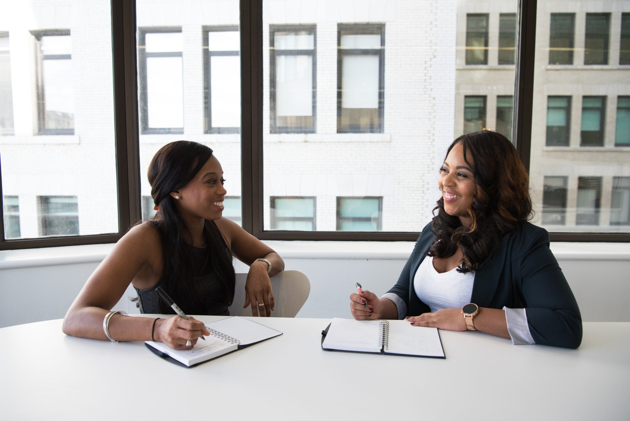 Two women meeting and taking notes