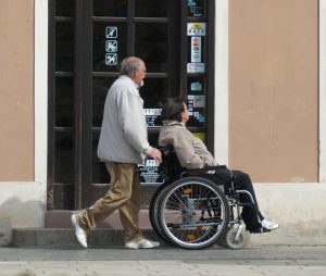 Woman on wheelchair with man outside a shop