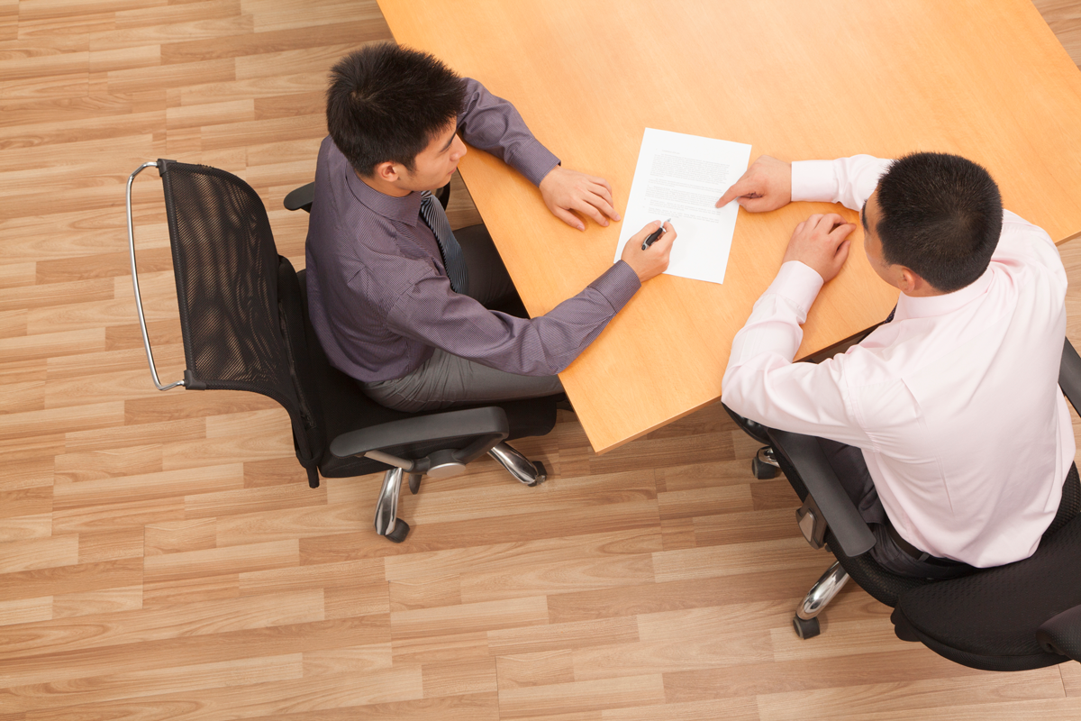 two male colleagues-signing-paperwork